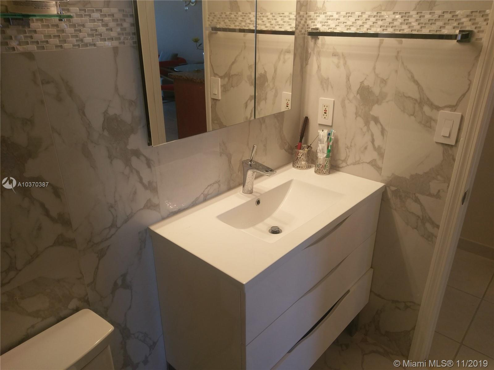 Photo of 2030 Ocean Dr #716, Hallandale, Florida, 33009 - ELEGANT EURO STYLE BATHROOM WITH FLOOR-TO-CEILING CARRERRA MARBLE AND GLASS MOSAIC DECORATIVE TILES AND CUSTOM RAIN SHOWER ENCLOSURE
