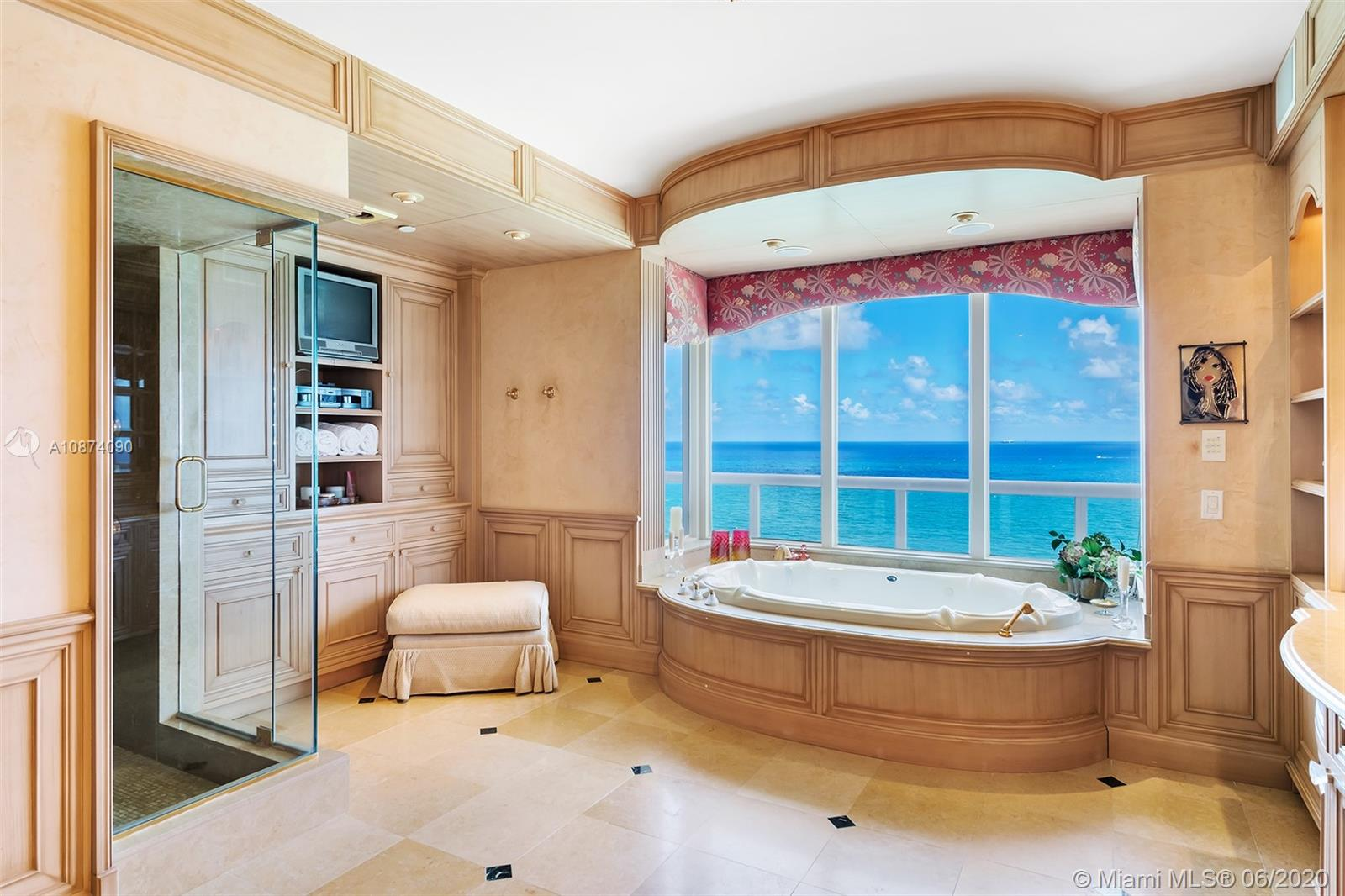 Photo of 6051 Ocean Dr #PH5, Hollywood, Florida, 33019 - Master bath features a whirlpool tub tucked in a bay window and separate shower