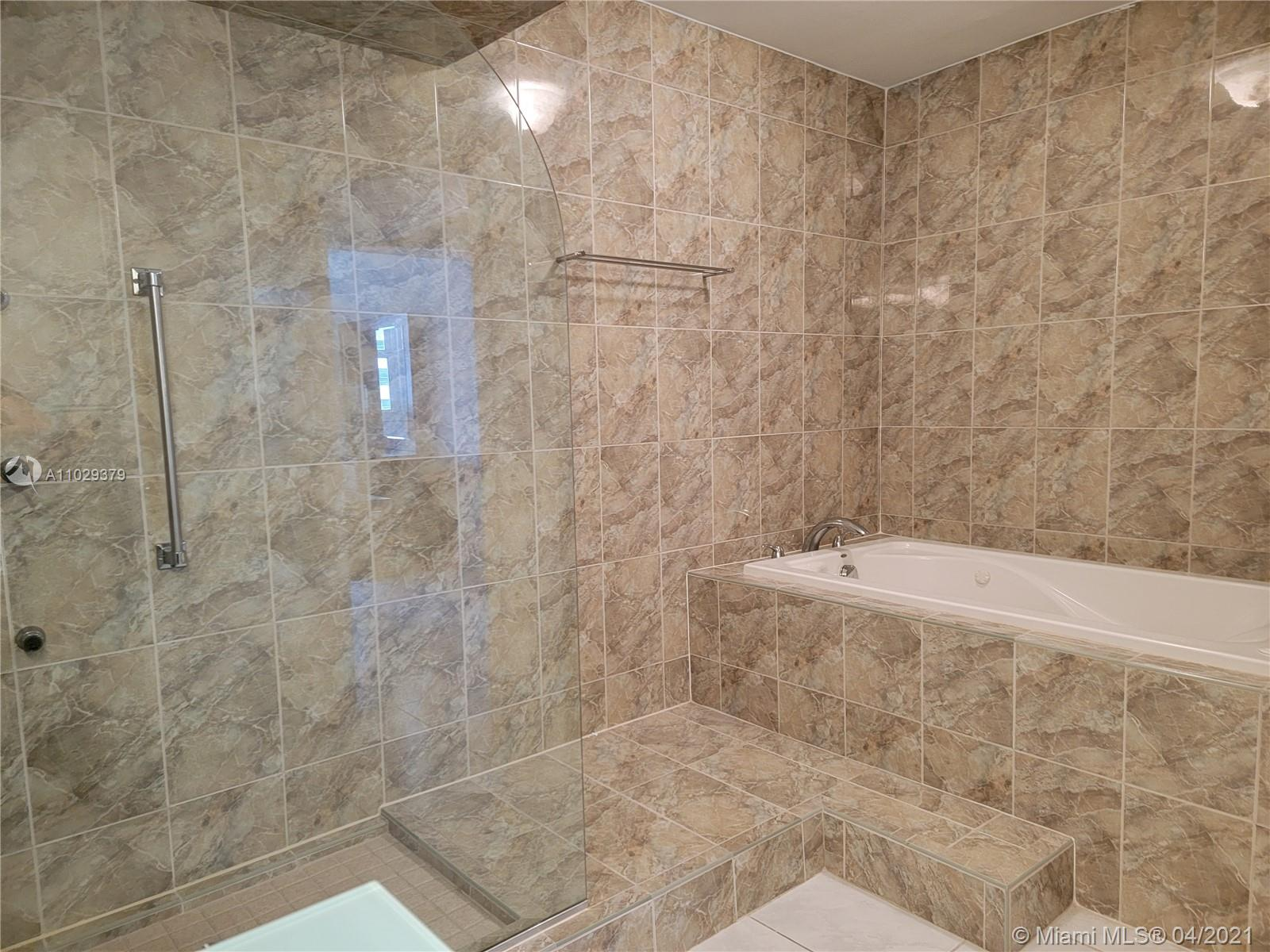 Photo of 2030 Ocean Dr #2026, Hallandale Beach, Florida, 33009 - Master Bathroom Floating Vanity Has 1 Piece Green Glass Top & Sink.  Walk In Shower with Euro Design Glass.